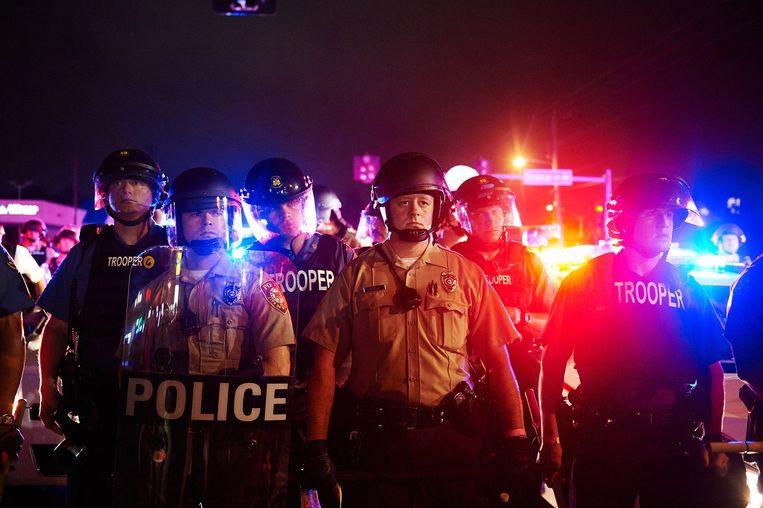 Politie tijdens een mars in Ferguson op 9 augustus ter herdenking van de dood van de 18-jarige Michael Brown, een jaar eerder. Beeld getty
