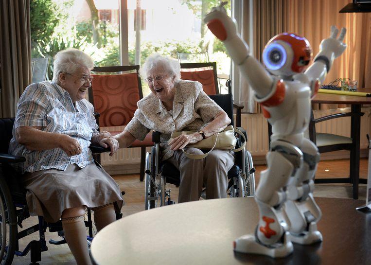 Twee oudere dames lachen om zorgrobot Zora. Beeld Marcel van den Bergh