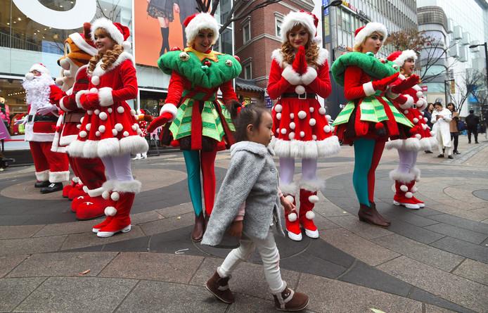 Een jong Zuid-Koreaans meisje loopt ogenschijnlijk ongeïnteresseerd langs vrouwen in kerstkleding. Foto Jung Yeon-Je