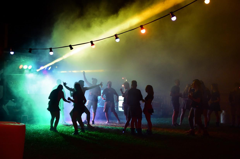 Jongeren bouwen een eigen festival in een weiland. Als iemand bij meerdere gelegenheden geen afstand hield, zie dan de bron nog maar te achterhalen. Beeld Marcel van den Bergh