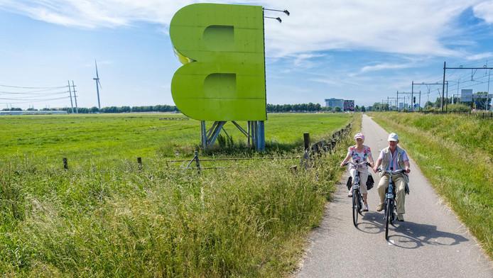 Kees en Maartje van Helden rijden op hun gemak langs Bleizo. Een fraaie uitgestrekte groene vlakte, waar inmiddels een en al bedrijvigheid had moeten zijn.