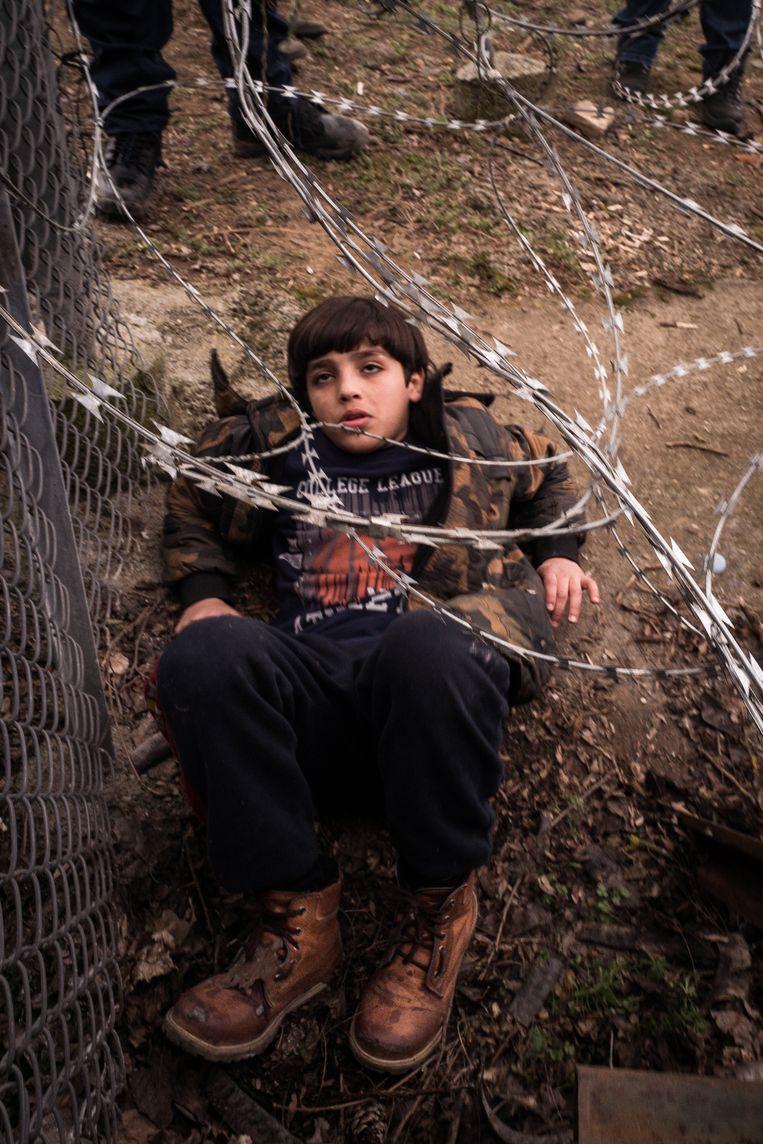 Een jongen probeert onder het prikkeldraad door te komen.  Beeld Nicola Zolin