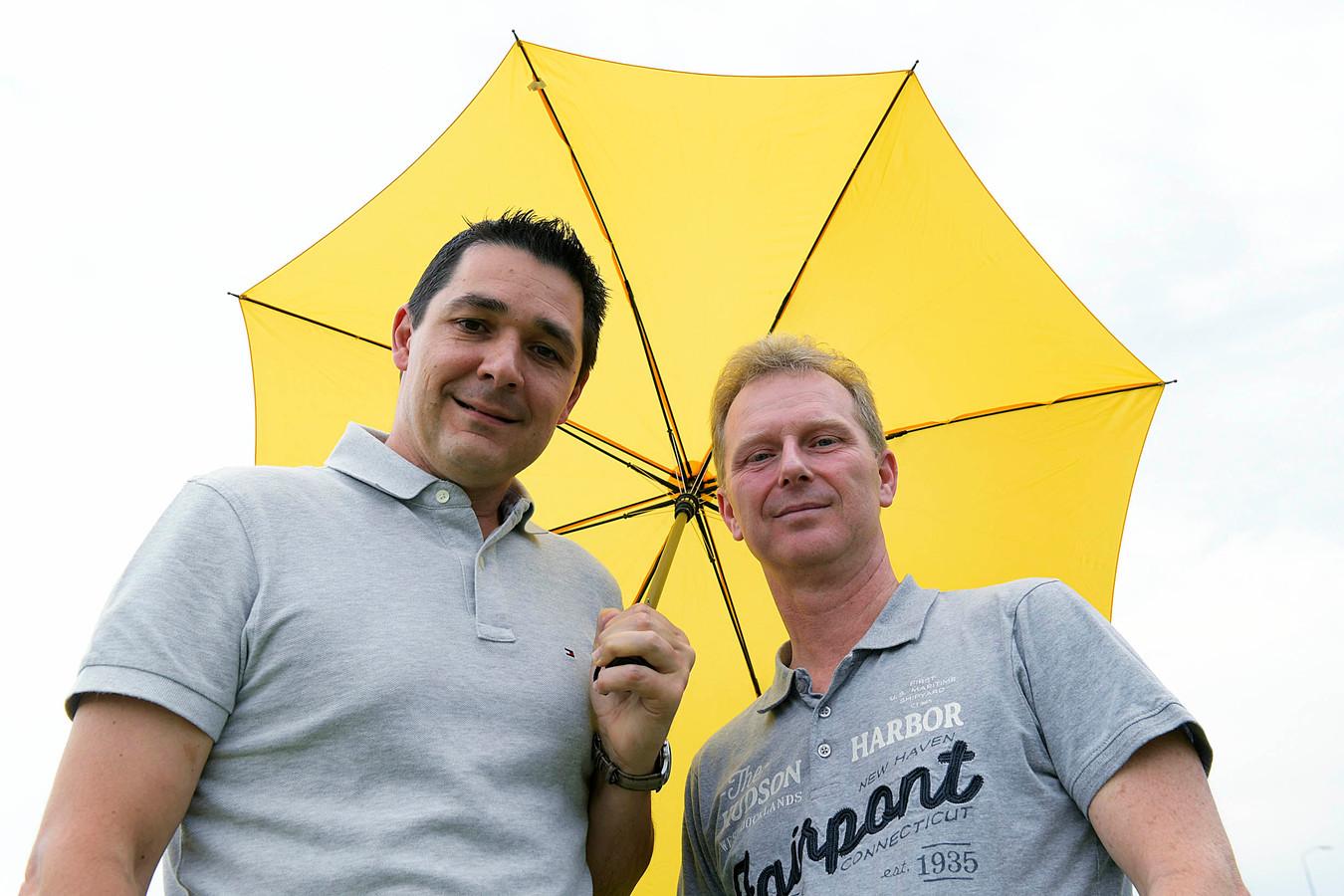 Mike Schram (links) en Erik Hoffman onder de paraplu. Samen met de voetballers van Dubbeldam willen de tafeltennis- en de korfbalvereniging een nieuwe accommodatie.