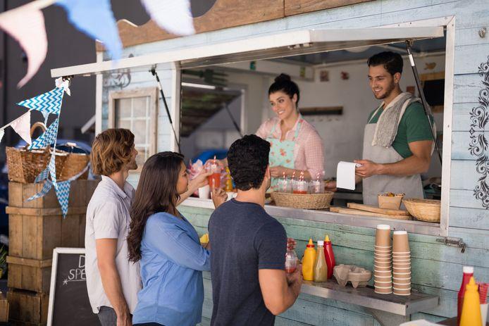Een glimlachende ober helpt zijn klanten in de foodtruck.