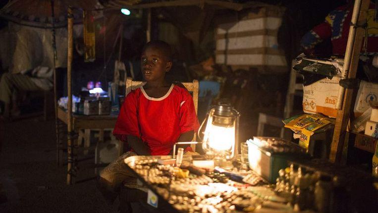 Een jongen zit naast een winkeltje op straat in hoofdstad Bangui Beeld reuters