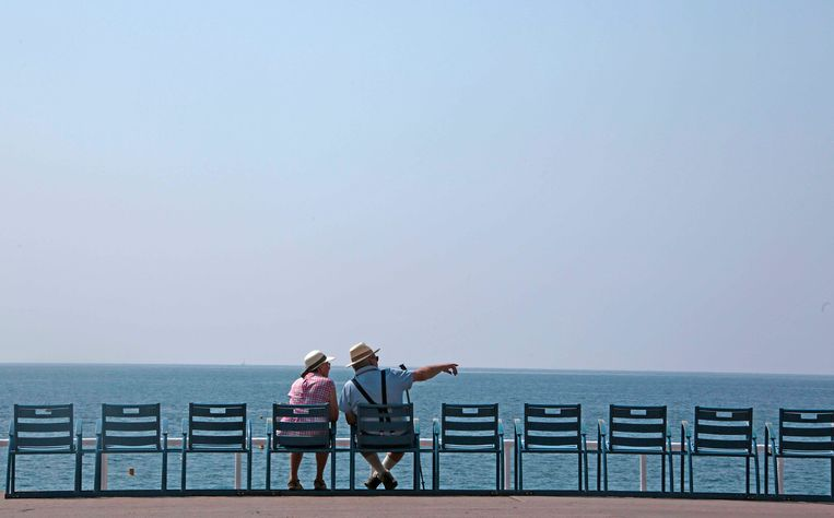 Twee oudere mensen zitten op een boulevard in Nice. Beeld Reuters
