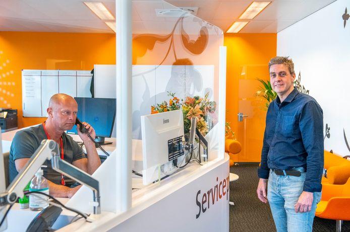 Jaap Pekaar van Pekaar Plastics leverde plexiglas voor onder meer het servicepoint van zorgverzekeraar CZ. Achter het scherm zit CZ-medewerker Jos van Bremen 'coronaveilig'.
