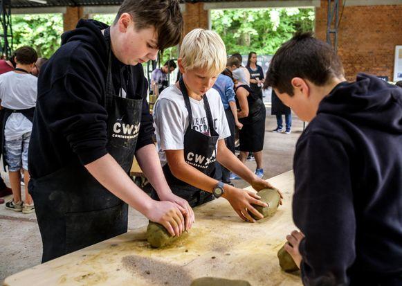 Kinderen boetseren de beeldjes en helpen zo kinderen in oorlogsgebied.