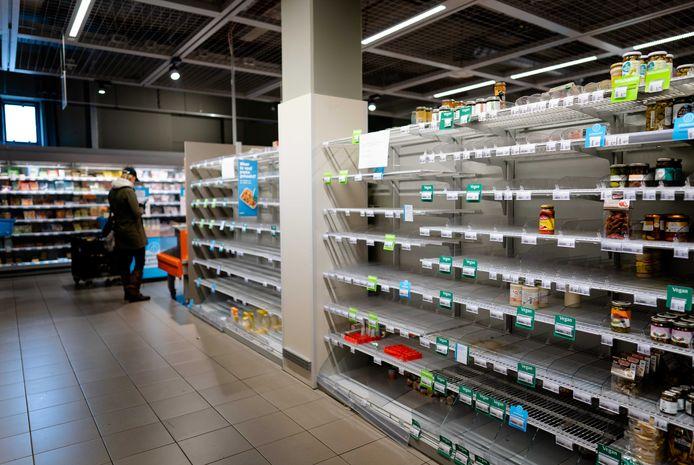 Lege schappen bij een filiaal van Albert Heijn in Amsterdam. Vooral pasta, wc-papier en groenteconserven worden ingeslagen.