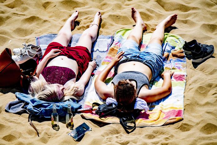 Zonaanbidders op het strand van Scheveningen. De temperatuur loopt komende week op tot boven de dertig graden.