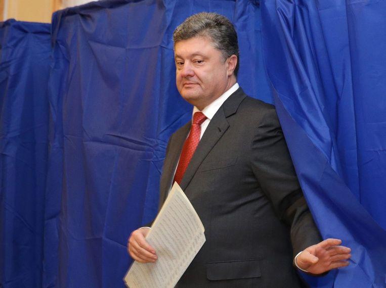 De Oekraïense president Petro Porosjenko verlaat het stemhokje. Beeld epa