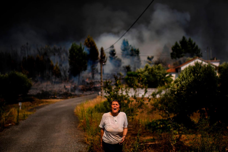 Een vrouw roept eind juli om hulp terwijl een bosbrand haar dorp, ten noordoosten van Lissabon, nadert. Ook dit weekend woedden in het land meer dan tweehonderd branden.