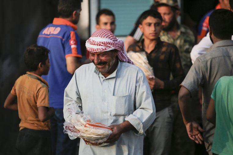 Syriërs in Ayn al-Arus komen brood halen.