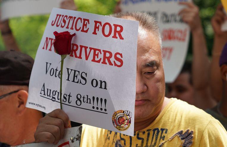 De vakbond voor taxichauffeurs in New York pleitte dinsdag voor wetgeving tegen de taxi-apps in een demonstratie bij het stadhuis. Ook steunt de organisatie families van taxi-chauffeurs die zelfmoord hebben gepleegd uit financiële nood. Beeld AFP