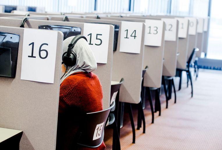 Een mevrouw maakt een inburgeringsexamen op een toetslocatie van Dienst Uitvoering Onderwijs (DUO).  Beeld ANP XTRA