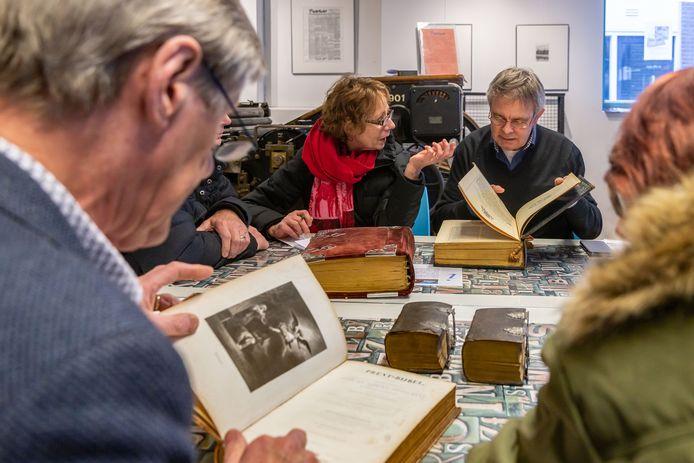 Taxatie van oude bijbels in Drukkerijmuseum, taxateur Otto Middendorp bekijkt een meegebrachte bijbelvan de familie Nas. Die wordt later op 300 euro geschat.