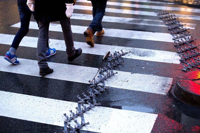 Een spijkermat op een zebrapad in het centrum van Brussel vanwege verhoogde terreurdreiging in de Belgische hoofdstad. Beeld anp