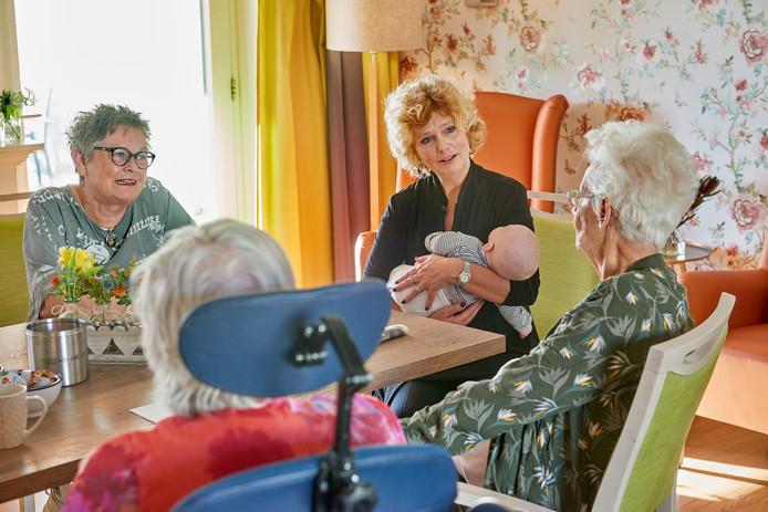 Jaqueline Pas en (links) en Loes Ofman met baby Bram feliciteren Ria Neddermeijer (rechts) in hospice De Goudsbloem in de Watersteeg.