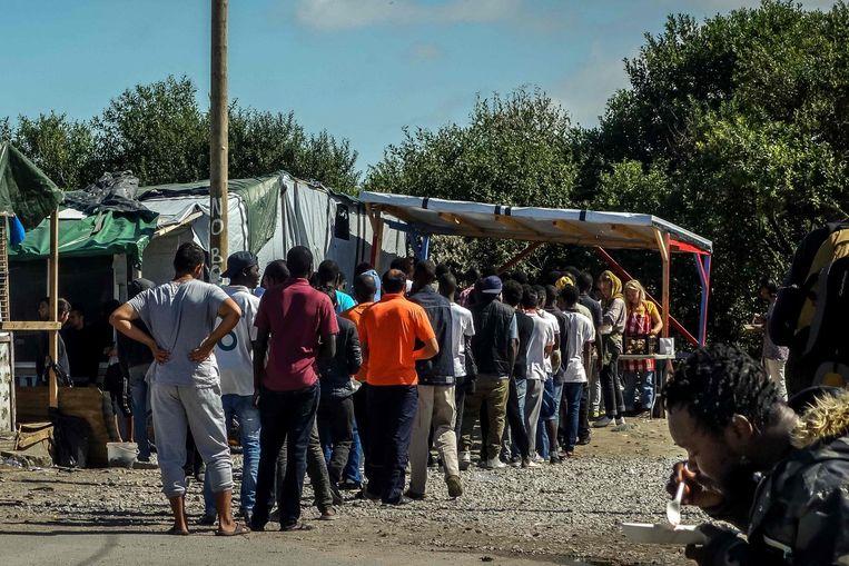Migranten staan in de rij voor eten Beeld afp