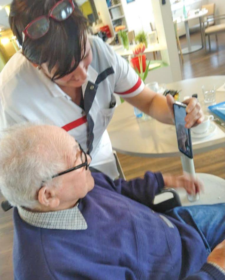 Een bewoner van rusthuis De Spoele krijgt hulp van een medewerkster om te bellen met familie, mét video erbij.