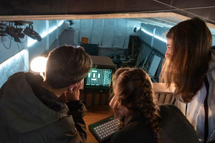 Bezoekers Wietse Cronenberg (l.) en zijn zussen Floor en Noa proberen de code te kraken.