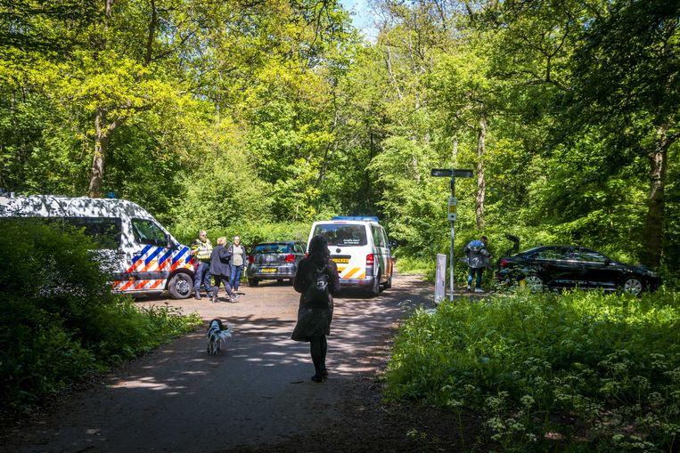 Politieagenten ondervragen passanten in het gebied waar een 56-jarige vrouw op gewelddadige wijze om het leven is gekomen. Het lichaam van de vrouw werd op het Galgenpad in de Scheveningse Bosjes aangetroffen.  Beeld ANP