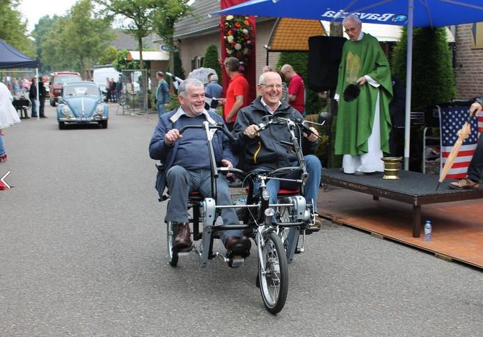 Wethouder van Rinsum (rechts) achter het stuur van de Zijtaartse duofiets.