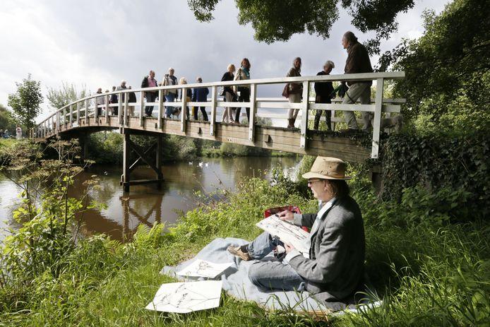 Bij Plein-Air aan de Mark zijn kunstenaars in het Markdal in de open lucht aan het werk, terwijl publiek langs loopt