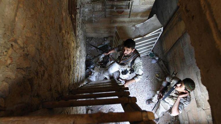 Syrische rebellen beklimmen een ladder in een huisje op het platteland nabij Aleppo. Beeld reuters