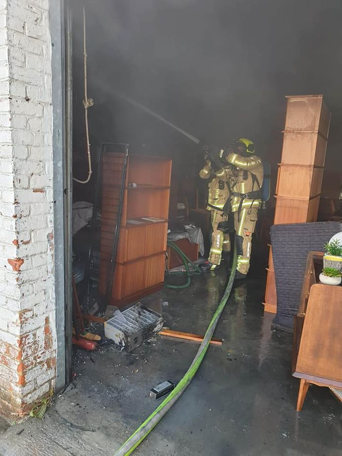 De brandweer aan het werk tijdens het blussen van de brand op de Paul Gilsonlaan in Drogenbos.