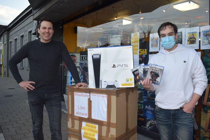 Michael Brandt (links) van multimediastore l'Obcédé aan zijn geïmproviseerde kartonnen afhaalbalie. Klant Gunther Bauwens heeft zijn PlayStation 5 te pakken.