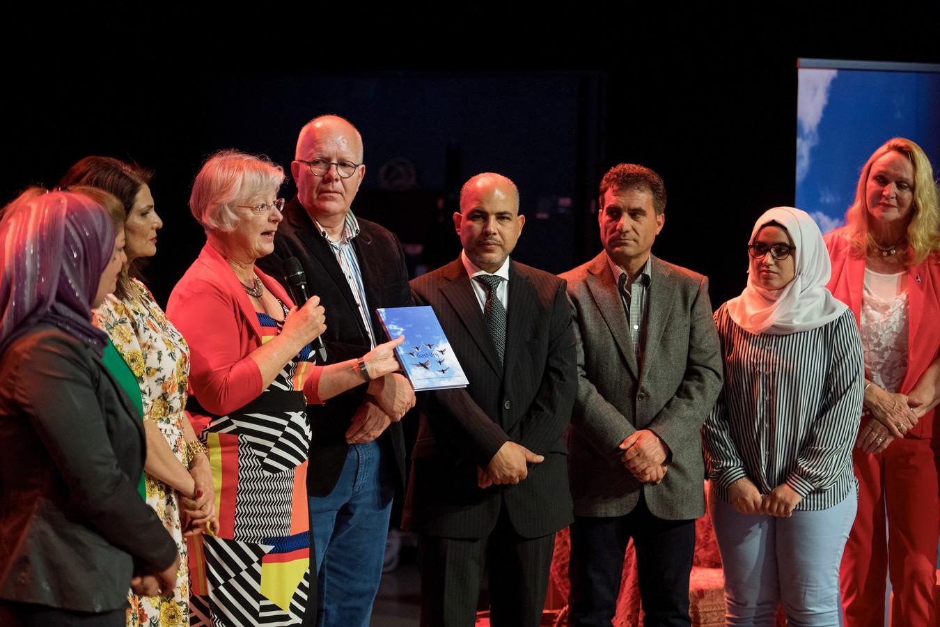 Gedeputeerde Josan Meijers (vierde van links) krijgt het boek Gast-Vrij uit handen van Zeger Visser (rechts naast haar).