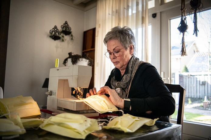 Jeanne van Ooijen is bezig met het maken van mondkapjes.