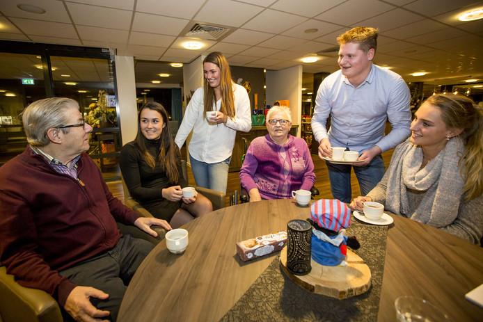 De Koffie Club Oldenzaal op bezoek bij ouderen. Tweede en derde van links Jamie Kerpisci en Ruth Harmelink.