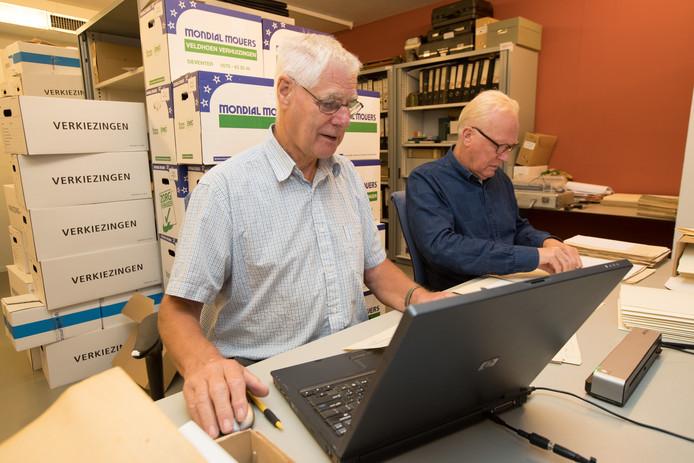 Geert Hannink (links) en Jan Westenenk, bestuursleden van de Historische Vereniging Raalte en Omstreken, verrichten monnikenwerk in de kelder van het gemeentehuis. Zij hebben op datum gerangschikte documenten uit de periode 1812-1924 gerubriceerd en gedigitaliseerd.