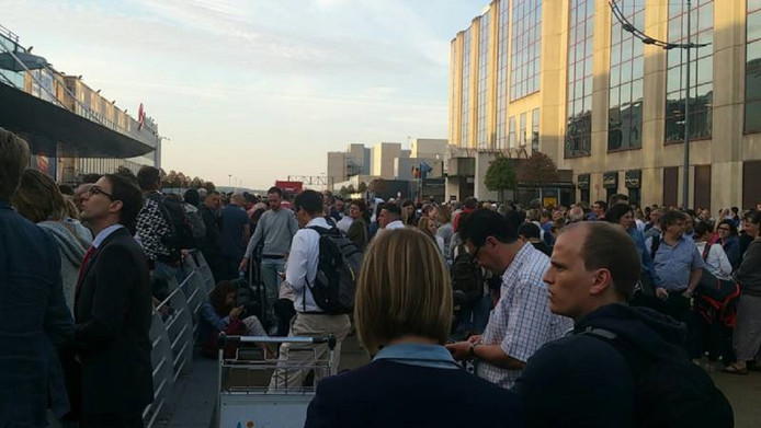 Honderden mensen staan te wachten voor het hoofdgebouw op de luchthaven.