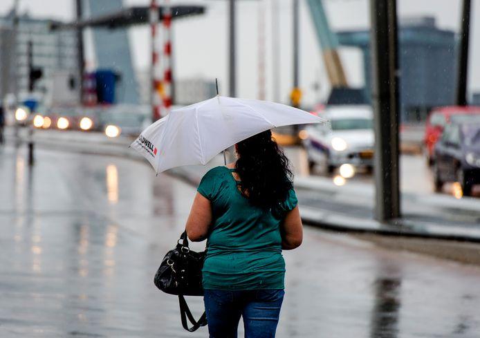 Een voetganger op de Erasmusbrug trotseert de regen.
