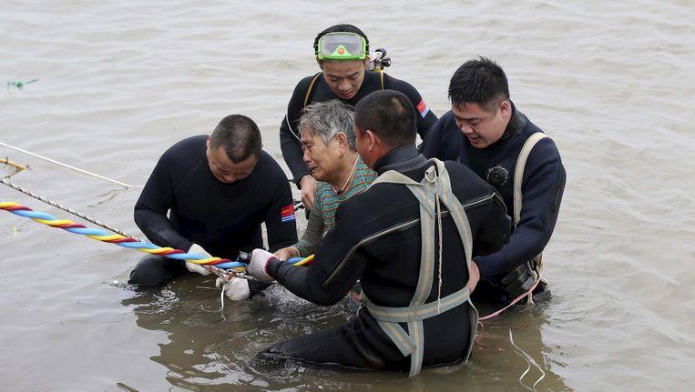 Een overlevende van de bootramp in China wordt door reddingswerkers uit het water geholpen. Beeld Reuters