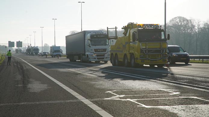 De vrachtwagen met pech blokkeert een weghelft, waardoor er achter een flinke file is ontstaan.
