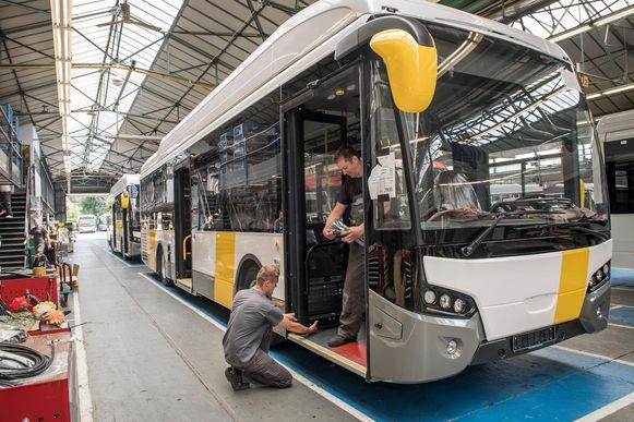 Een blik op de productielijn: twee arbeiders plaatsen de deur van een bus.