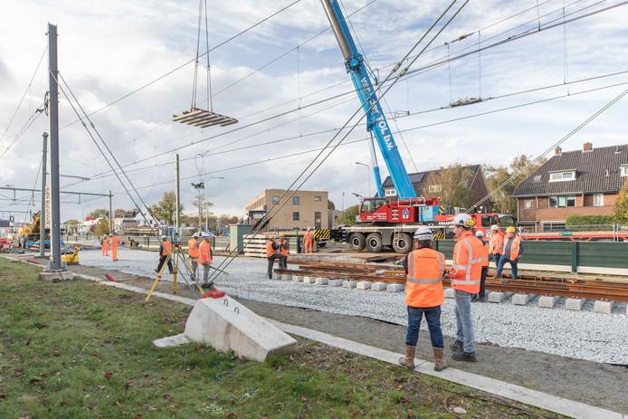Het krioelt van de oranje hesjes bij de spoorwegovergang aan de Kloetingseweg.