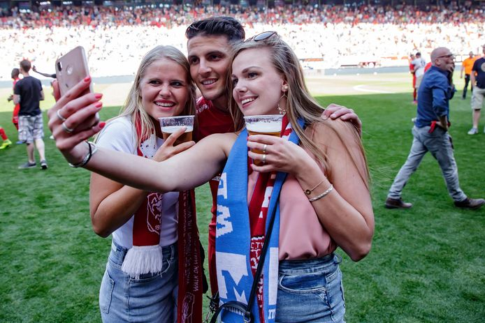 Rafik Zekhnini viert het behalen van de titel met bierdrinkende Twente-fans.