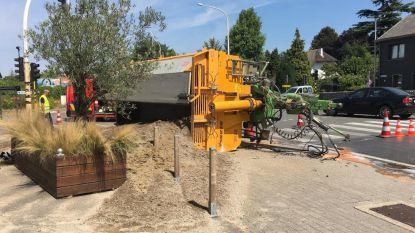Tractor kantelt, inhoud laadbak belandt op terras brasserie
