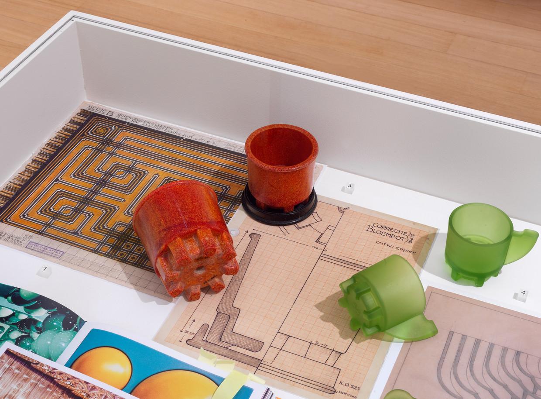 Cup and Paste van Bas van Beek in een vitrine met enkele inspiratiebronnen, waaronder bloempotten van A.D. Copier en een tapijtontwerp van K.P.C. de Bazel.