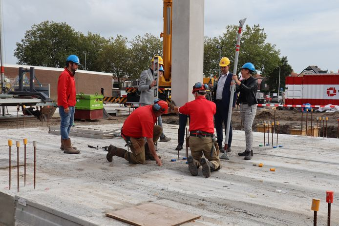 Start van de bouw door wethouder Koning, bouwers en kopers met het plaatsen van een prefab kolom.