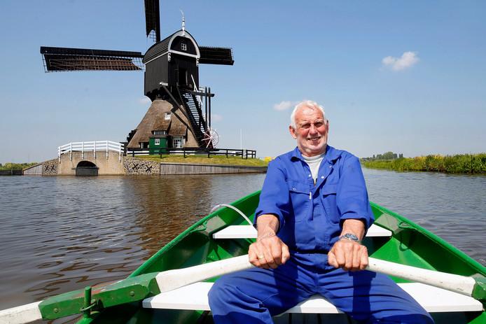 Cees Noorlander in zijn bootje met zijn molen op de achtergrond. Onder: ,,Er is altijd wat te doen aan de molen'', zegt Noorlander.