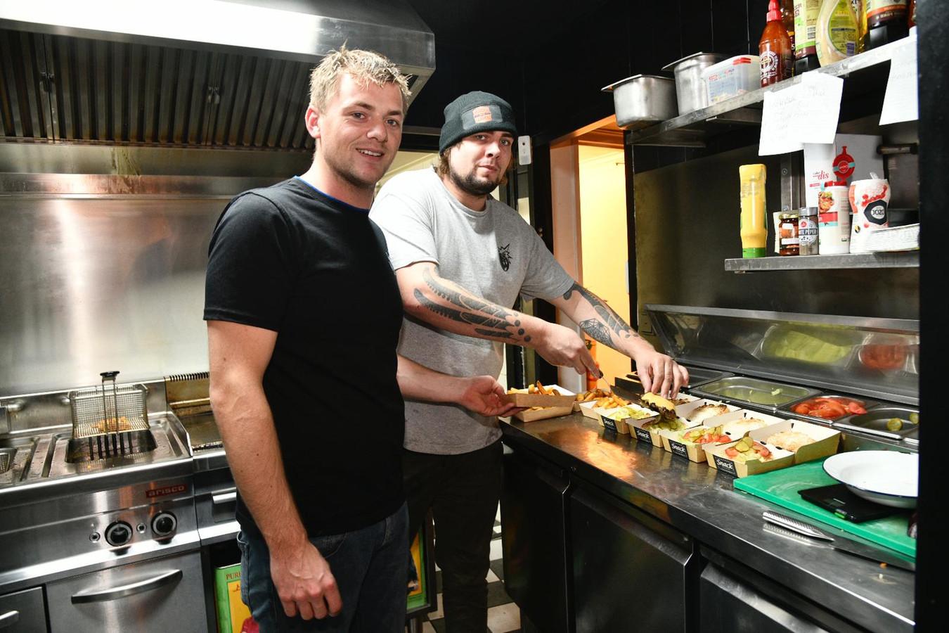 Jort Brink (r) en zijn medewerker Rik Janszen zijn alweer druk bezig met het klaarmaken van afhaalmaaltijden.