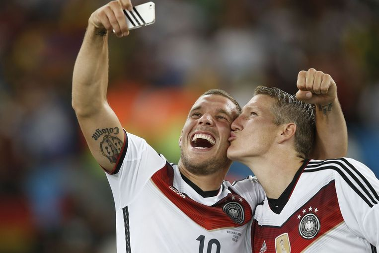 Lukas Podolski (links) en Bastian Schweinsteiger na de gewonnen WK-finale, 13 juli 2014. Beeld afp