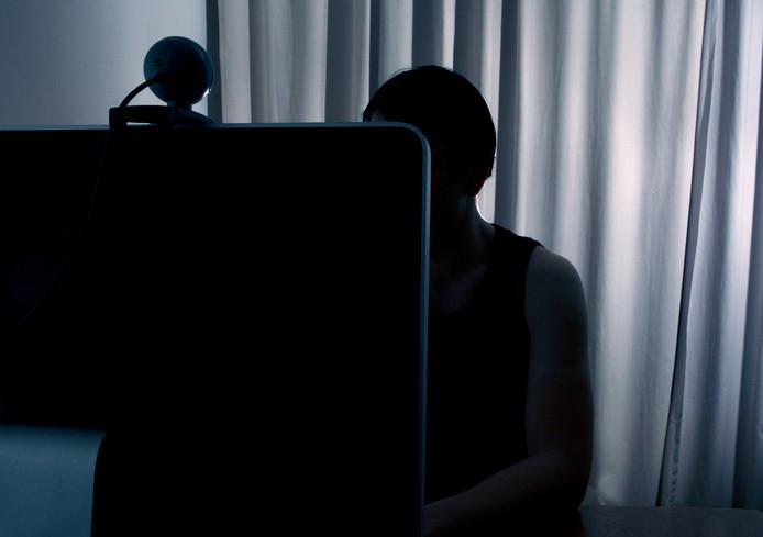 Een man kijkt naar zijn webcam.