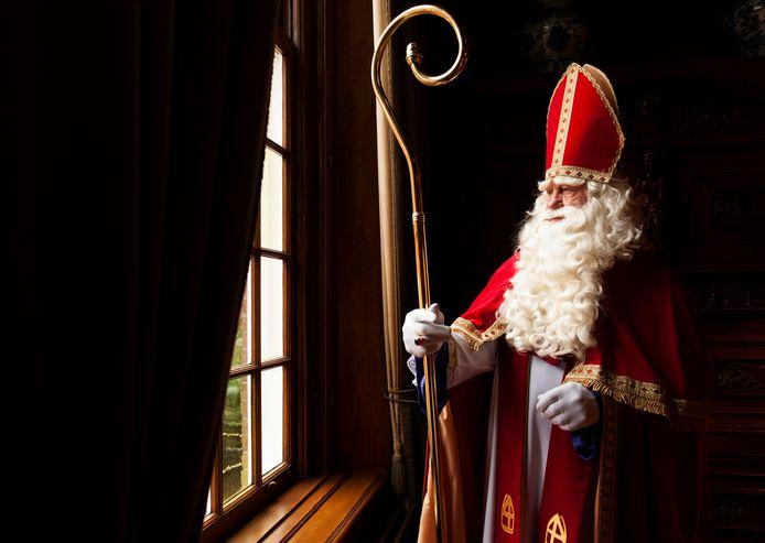 Sint kijkt uit het raam van zijn kasteel.